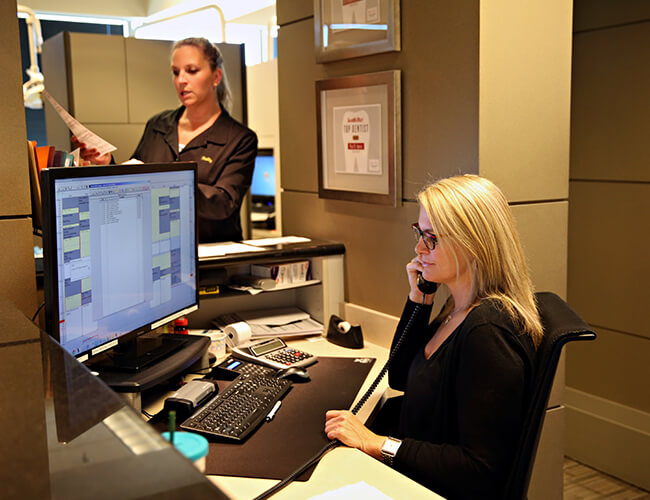 Our front desk staff on a phone call in front of the computer