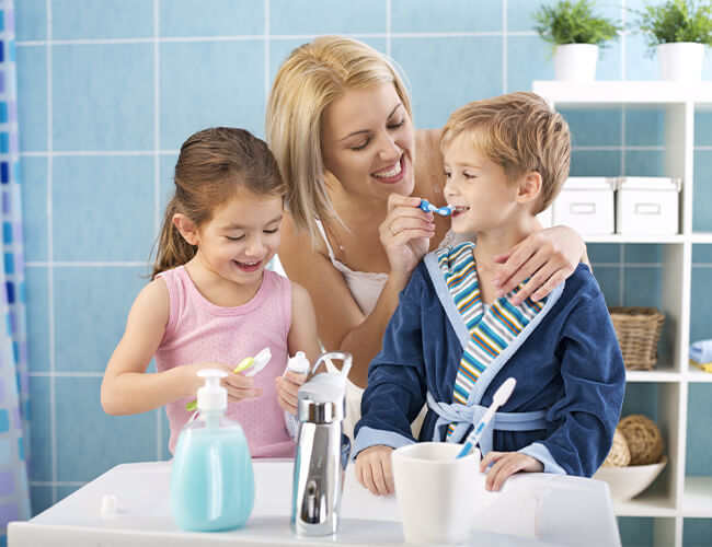 A mom showing her son and daughter how to brush their teeth