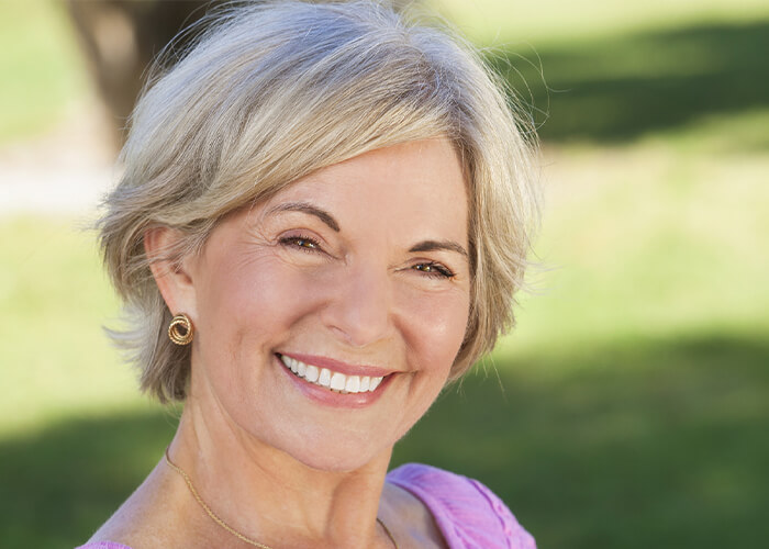 Older woman smiling outdoors
