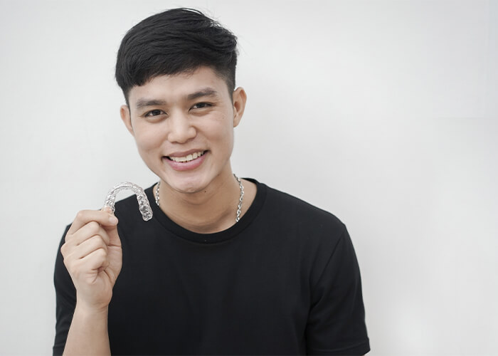 A young man holding his Invisalign clear aligners