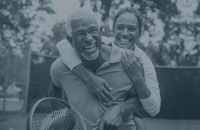 Image of a mature couple playing tenis