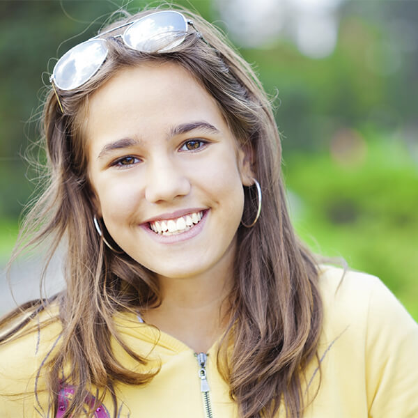 A young woman in a yellow sweater smiling outside