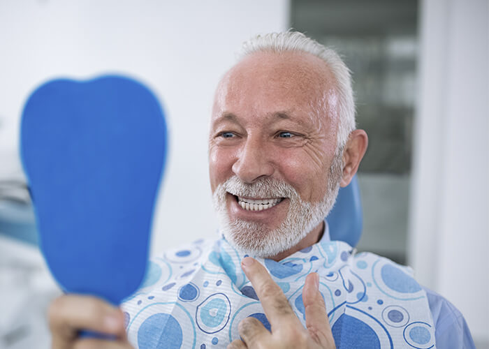 An older man checking his smile in a mirror