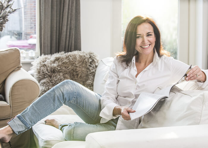 Middle aged woman lounging comfortably on a sofa